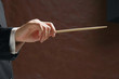 A concert conductor's hand with a baton, isolated on a black