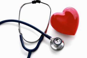 Red heart and a stethoscope lying at the desk, isolated on white