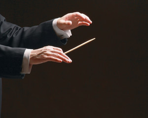 Concert conductor's hands with a baton, isolated on a black