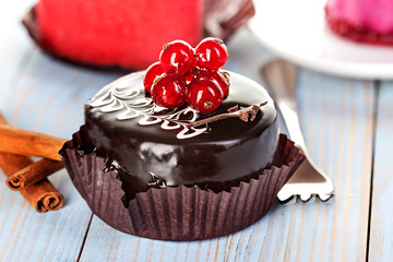 Chocolate cake with red currants on a wooden background