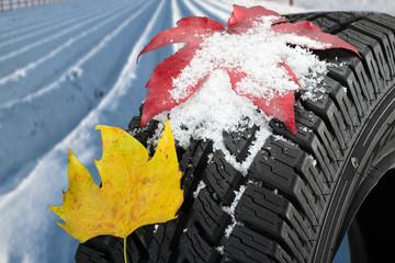 Winterreifen mit Schnee und Herbstblatt