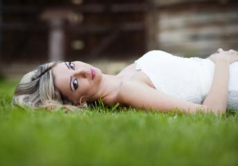Blonde bride lying on grass