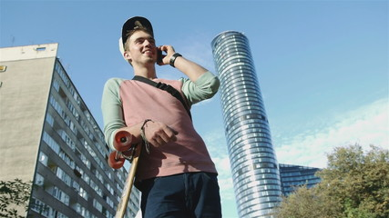 Young cheerful boy with longboard talking on phone in the city.