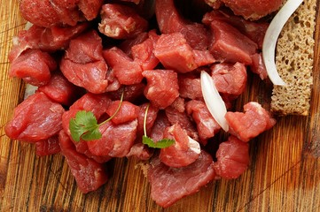 beef cut into cubes on a wooden background