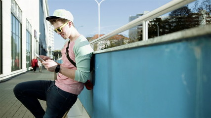 Stylish teenager using tablet in a city street during sunny day.