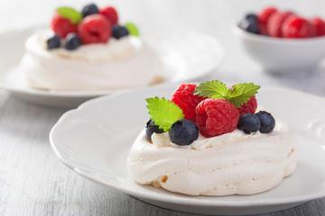 pavlova meringue cake with cream and berry