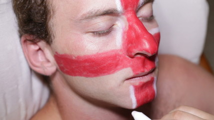 Closeup of a man face painting flag of United Kingdom.