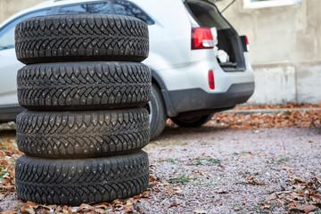 Four winter tyre wheels are near suv, copyspace