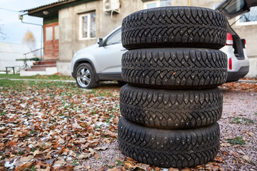 Four winter tire wheels ready for changing near car, copyspace