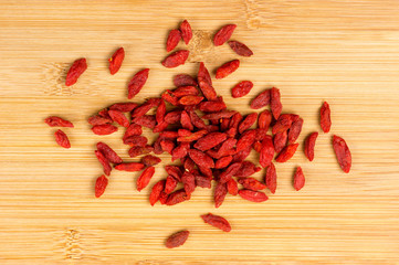 Pile of dry goji berries on a wooden board