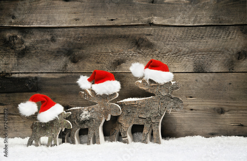 Leinwanddruck Bild Three mooses wearing santa hats on grey wooden background