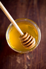 Honey jar with honey spoon on a wooden table