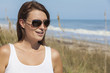Woman in White Dress and Sunglasses At Beach