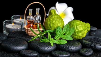 Aromatic spa of bottles essential oil in basket, fresh mint, ros