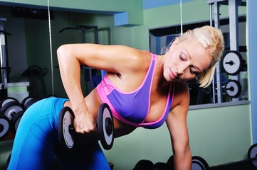Beautiful muscular woman exercising in a gym