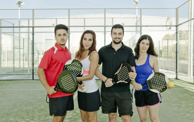 Paddle tennis couples posing for macht