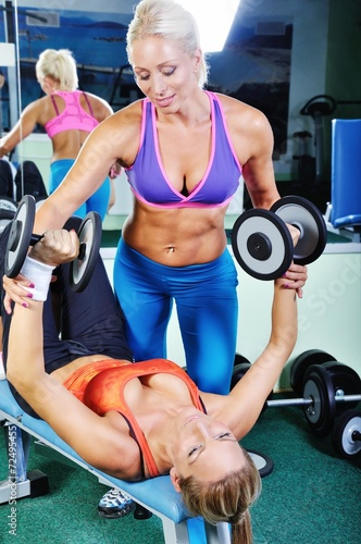 Fototapeta Beautiful women exercising with personal fitness trainer