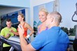Two women in gym exercising with personal fitness trainer