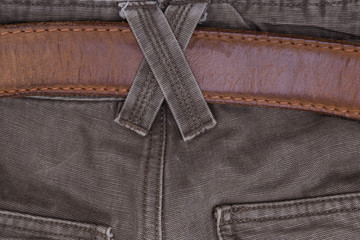 Brown jeans with a belt and binding. Close-up of men's clothing.