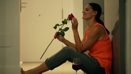 Happy woman sitting on the floor and smelling red rose