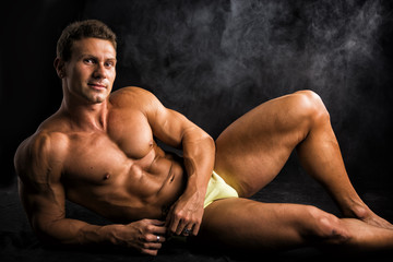 Handsome shirtless muscular man laying down on the floor