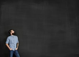Bearded man looks at chalkboard