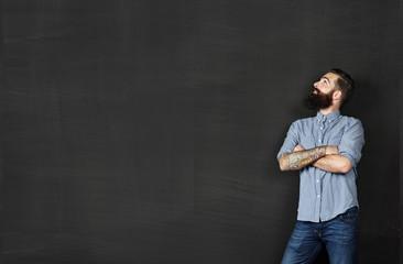 Tattooed man looking chalkboard