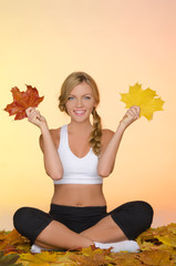 young woman sitting practices yoga in fall