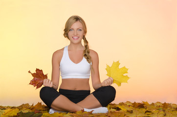 smiling woman sitting practices yoga in fall