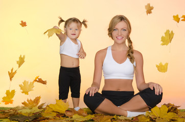 beautiful woman and child do yoga under leaves