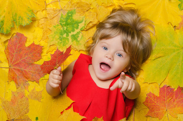 child in red dress in yellow leaves.