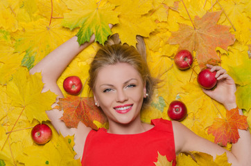 beautiful woman in yellow autumn leaves and apples
