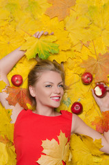 beautiful woman in yellow leaves and apples