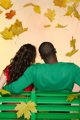 black man and asian woman under leaf fall from