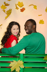 black man and asian woman under the leaves