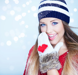 Woman wearing winter hat and gloves covered with snow flakes