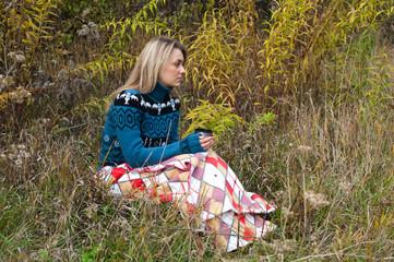 Девушка в пледе на поляне