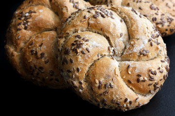 Whole wheat kaiser rolls with sesame seeds on black surface.