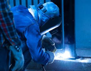 Welder repairing the metal fence