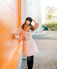 Street fashion, pretty woman model in coat and hat posing outdoo