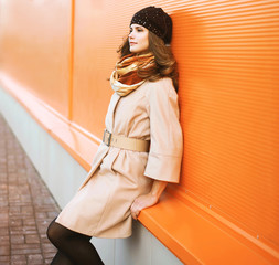 Street fashion portrait pretty girl in coat and hat posing again