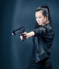 Asian young woman with a gun