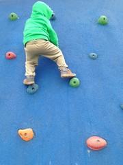 Kind klettert auf Kletterwand