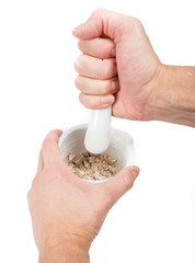 Person crushing brown sugar cubes in a white marble mortar