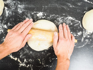 Person handling a dough with a rolling pin floured black table