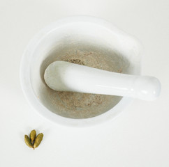 White marble mortar with whole cardamom on the side