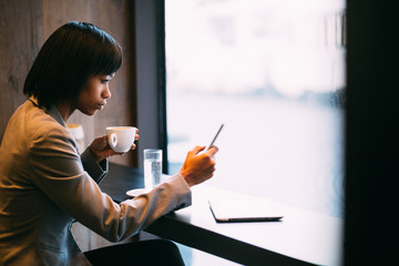 Young businesswoman using phone in coffee shop