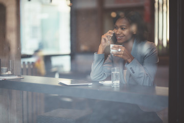 Young businesswoman talking on phone in coffee shop