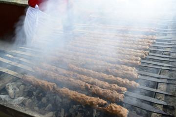 Shish kebab is cooked on  coals outdoors