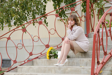 The girl with a bouquet of yellow roses sitting on stairs
